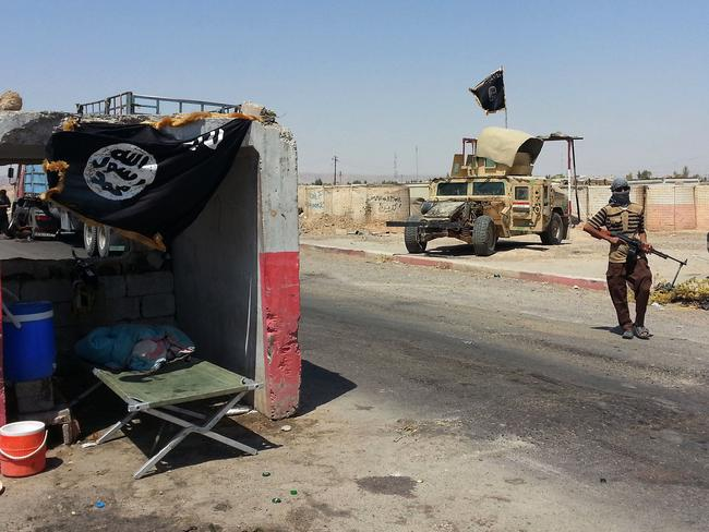 Taking over ... an al-Qaida inspired militant stands with a captured Iraqi Army Humvee at a checkpoint outside Beiji refinery, some 250km north of Baghdad.