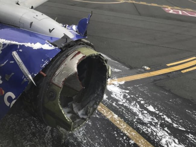 The engine on a Southwest Airlines plane is inspected as it sits on the runway at the Philadelphia International Airport after making an emergency landing. Photo: Marty Martinez / AP