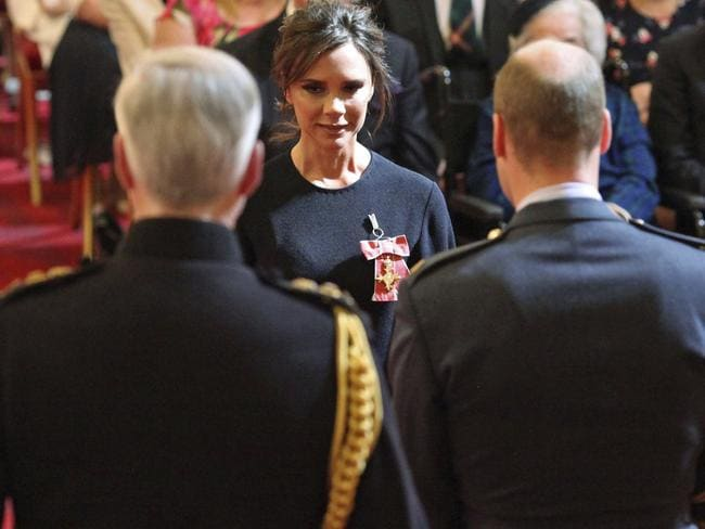 Fashion designer Victoria Beckham, background centre, receives her OBE from Britain's Prince William, the Duke of Cambridge during an investiture ceremony at Buckingham Palace in London.