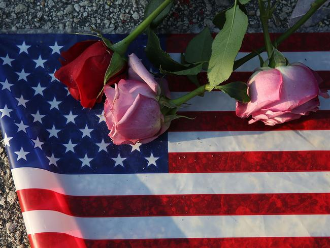 Flowers and an American flag are seen on the ground near the Pulse Nightclub whe-re Omar Mateen killed 49 people on June 13, 2016 in Orlando, Florida.
