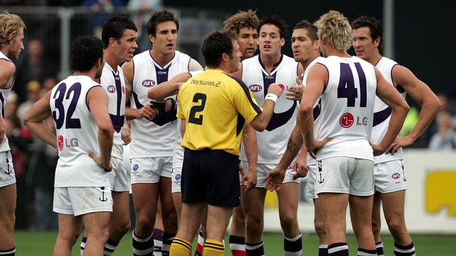 Fremantle players surround umpire Michael Vosso after the final siren. Picture: George Salpigtidis
