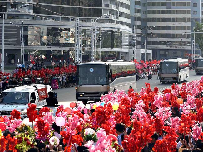 People greet buses carrying developers of the ground-to-ground medium-to-long range strategic ballistic rocket Hwasong-12 in Pyongyang on May 18.