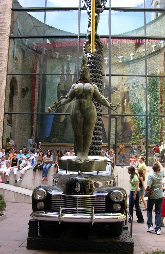 The stone walls of the patio inside the Dali Theatre-Museum with Salvador Dali's wife Gala's black Cadillac car with a bronze statue of Esther Queen by Ernst Fuchs towering above it in Figueres, Spain.