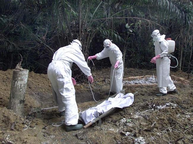 Workers wearing protective clothing bury five-year old Adamou, next to the graves of other Ebola victims in the cemetery Friday Dec. 28, 2001 in Mekambo, north eastern Gabon.