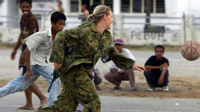 An Australian female soldier plays with East Timorese boys in Dili in 1999. (Pic: Supplied)