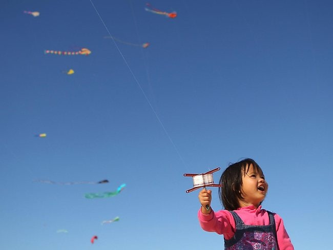 A young girl flies a kite during the annual Festival of the Winds festival on Bondi Beach, Australia's largest kite flying festival.