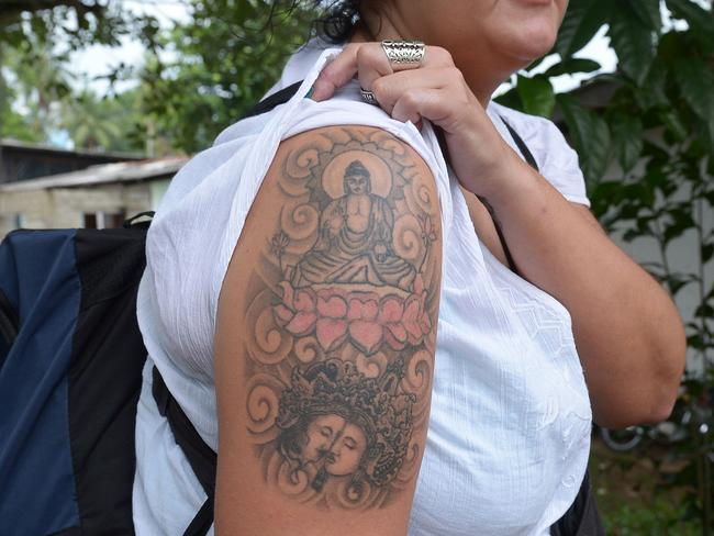 "(FILES) This file photo taken on April 22, 2014 shows British tourist Naomi Coleman posing for a photograph to display a tattoo of the Buddha on her upper arm, after she was arrested at Sri Lanka's main international airport and later ordered with deportation for having a tattoo of the Buddha, in Colombo. Sri Lanka's top court on November 15 awarded compensation to a British woman arrested for sporting a Buddha tattoo, saying the nurse was subjected to ""horrifying and scandalous treatment"" by local authorities. Naomi Michelle Coleman was detained in prison in 2014 after touching down in Colombo, where police in the Buddhist-majority country took offence to the tattoo on her arm.  / AFP PHOTO / Lakruwan WANNIARACHCHI"