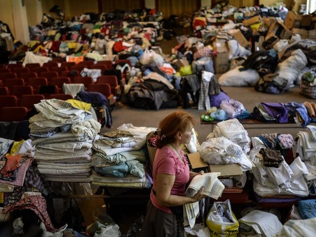 Preparing for something ... a woman checks clothes piled up in a room of a building occupied by pro-Russian separatists in Donetsk. Picture: Bulent Kilic