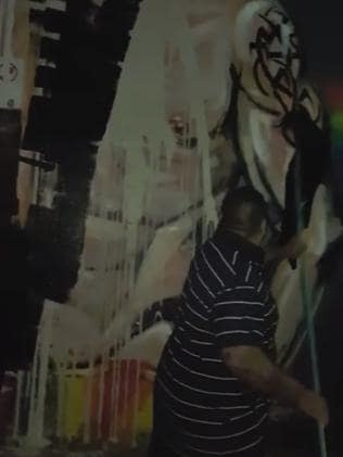 A man is seen painting over the mural.
