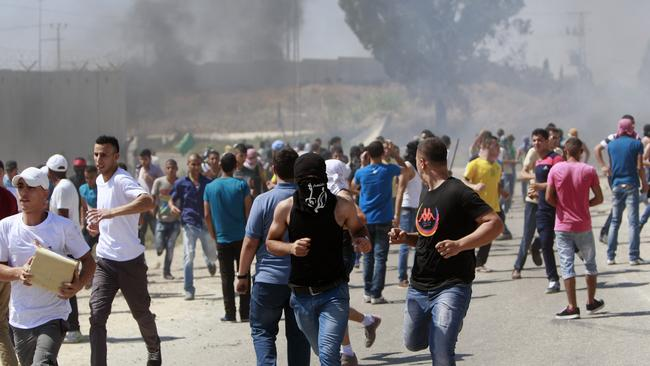 Palestinians run for cover ... following a protest against the war in the Gaza strip, during clashes near the West Bank town of Tulkarem. Picture: AP Photo/Mohammed Ballas