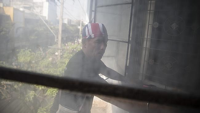 An anti-government protester looks into a window from a ledge of a building as they search dilapidated homes for possible suspects Picture: AP