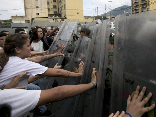 University students push on the riot shields of Venezuelan Bolivarian National guards officers during a protest outside of the Supreme Court in Caracas, Venezuela. Picture: AP