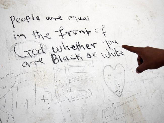 An illegal sub-Saharan migrant shows writings on a wall as he waits at the Qanfouda detention centre, in the southern outskirts of Benghazi. Picture: Abdullah DOMA