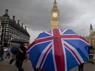 TOPSHOT - A pedestrian shelters from the rain beneath a Union flag themed umbrella as they walk near the Big Ben clock face and the Elizabeth Tower at the Houses of Parliament in central London on June 25, 2016, following the pro-Brexit result of the UK's EU referendum vote. The result of Britain's June 23 referendum vote to leave the European Union (EU) has pitted parents against children, cities against rural areas, north against south and university graduates against those with fewer qualifications. London, Scotland and Northern Ireland voted to remain in the EU but Wales and large swathes of England, particularly former industrial hubs in the north with many disaffected workers, backed a Brexit. / AFP PHOTO / JUSTIN TALLIS