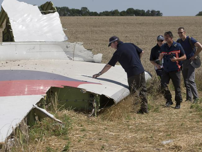 At the scene ... Australian and Dutch investigators examine a piece of the Malaysia Airlines Flight 17 plane, near the village of Hrabove, Donetsk region, eastern Ukraine. Picture: AP Photo/Dmitry Lovetsky