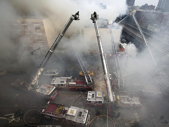 Devastation ... Firefighters respond to an explosion that levelled two apartment buildings in the East Harlem neighbourhood of New York.