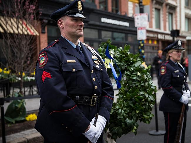 Remembrance ... officers stand guard next to a wreath marking one of the bombing sites on the first anniversary of the 2013 Boston Marathon Bombing. Picture: Andrew Burton