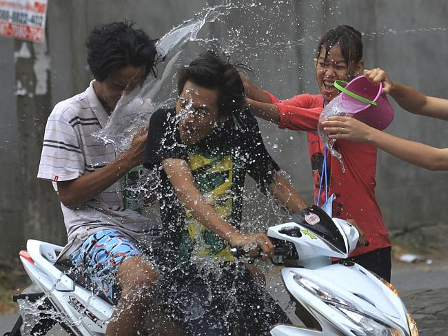 People riding on a motorbike are splashed with water during the Songkran festival in Bang