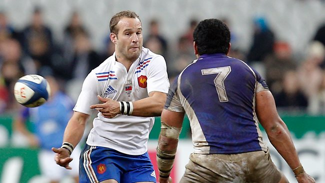 France's Frederic Michalak passes the ball next to Samoa's Maurie Faasavalu at the Stade de France stadium. Picture: Christophe Ena