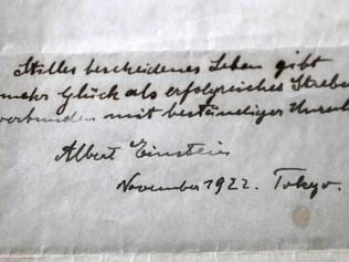 A picture taken on October 19, 2017, shows Gal Winner, owner and manager of the Winner's auction house in Jerusalem, displays one of two notes written by Albert Einstein, in 1922, on hotel stationary from the Imperial Hotel in Tokyo Japan. A note that Albert Einstein gave to a courier in Tokyo, briefly describing his theory on happy living, has surfaced after 95 years and is up for auction in Jerusalem. / AFP PHOTO / MENAHEM KAHANA