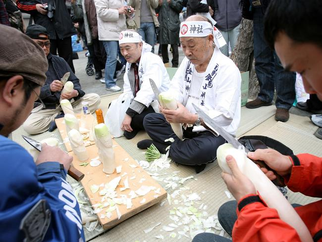 KAWASAKI, JAPAN - APRIL 05: Participants and visitors carve Japanese radishes into the shape of phallus during the Kanamara Festival, or the Utamaro Festival, at Wakamiya Hachimangu Shrine on April 5, 2009 in Kawasaki, Japan. The annual feritility festival, held traditionally in the cherry blossom season since the Edo era (1603-1868), is said to encourage fertility and bring harmony to married couples. In recent times the festival has raised awareness of AIDS prevention. (Photo by Kiyoshi Ota/Getty Images)