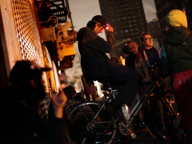 A man rides a bicycle to generate electricity so residents can charge their cell phones after Hurricane Sandy left them without power. Picture: AFP