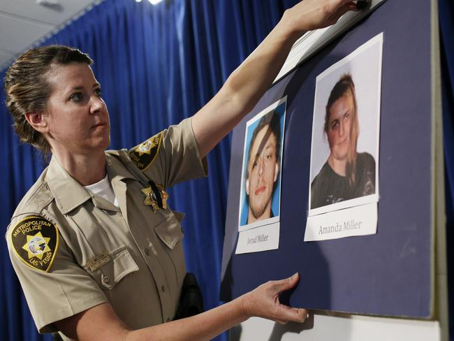 Children of the revolution ... A Las Vegas Metropolitan Police officer hangs up pictures of Jerad Miller and Amanda Miller before a news conference.