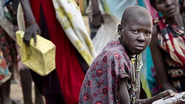Women displaced by recent fighting in South Sudan rest at a food distribution site in the