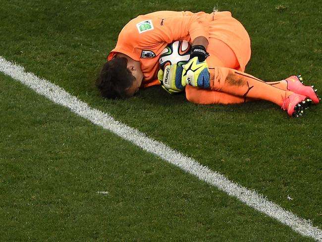 Uruguay's goalkeeper Fernando Muslera curls up in the foetal position after a fan yelled out that his orange outfit doesn't really match his skintone. AFP PHOTO / JUAN BARRETO