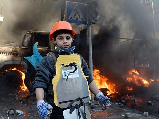 Innocence gone ... A young anti-government protester looks on during clashes with police in front of the Ukrainian Parliment, February 18. Picture: AFP Photo / Sergei Supinsky