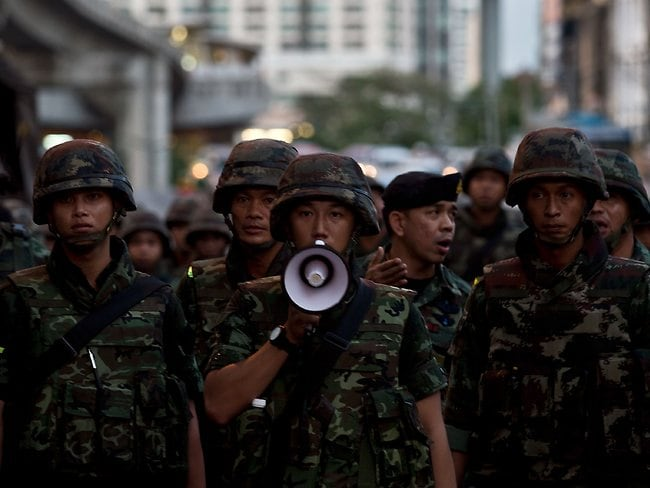 Muscling in ... Thai army soldiers urge anti-coup protestors to maintain law and order during a protest in downtown Bangkok.