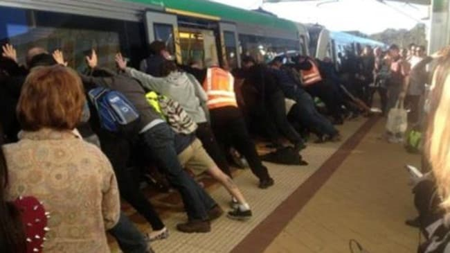 People power: Commuters helped free a man who got his leg stuck between a train and a platform. Picture: Renae Bryant