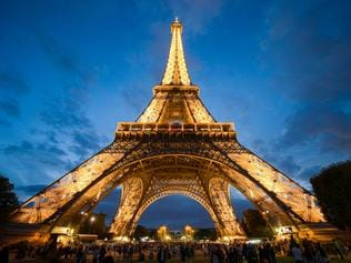Tourists are visiting the eiffel tower in the twilight in Paris in France