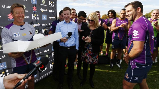 Craig Bellamy is presented with a cake by Cameron Smith before coaching his 300th game.