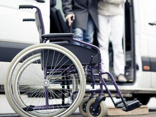 Generic image of an elderly patient being helped into a wheelchair by a nurse.