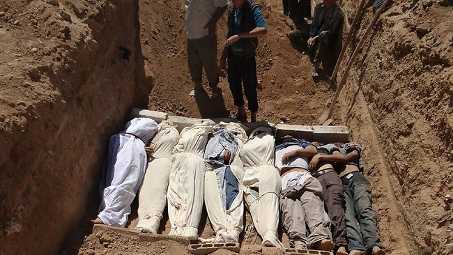 Several bodies being buried during a funeral in a suburb of Damascus, Syria.