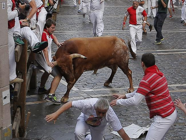A reveler is tossed by a Miura fighting bull during the running of the bulls at the San Fermin festival, in Pamplona, Spain, Monday, July 14, 2014. Revelers from around the world arrive to Pamplona every year to take part in some of the eight days of the running of the bulls. (AP Photo/Andres Kudacki)