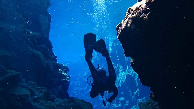 Silfra Rift off Iceland is the only place you can dive between, and touch the tectonic plates of both Eurasia and America. Picture: Iceland Explorer/Facebook.