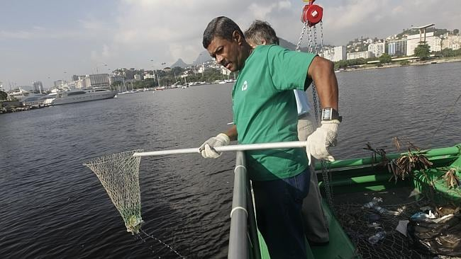 Dirty job ... A worker fishes out trash from a garbage-collecting barge at the Guanabara bay. Picture: Silvia Izquierdo