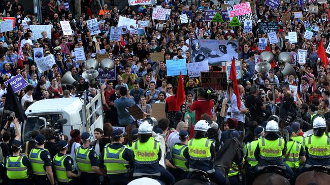 Police confront thousands of protesters at State Parliament.