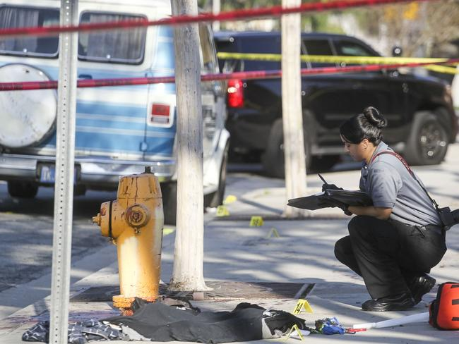 A police officer examines evidence at the crime scene. Picture: AFP