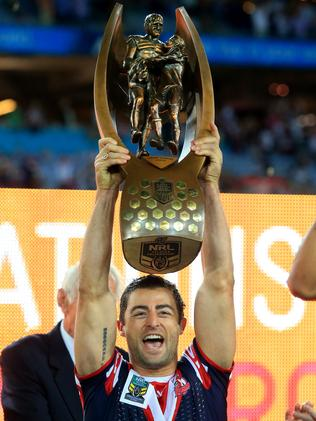Mini holds aloft the NRL trophy.