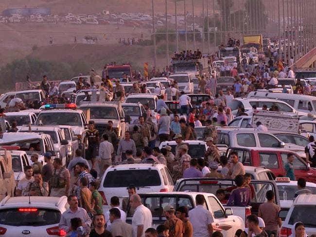 This image taken in August 2014 shows Yazidi people fleeing their homeland in Northern Iraq after the arrival of Islamic State. Thousands of women and girls were captured at the time and used as sex slaves for ISIS soldiers. Picture: AP Photo via AP video