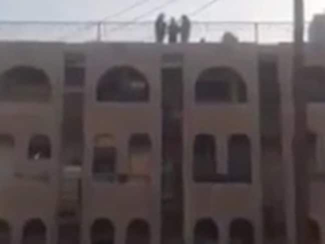 Three men stand atop a building in al-Raqqah before one is tossed to his death.