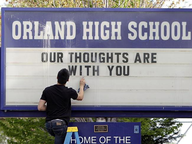In memory ... Sergio Parra, a 10th grader at Orland High School, cleans the glass on the school's sign after placing a memorial remembering the victims of the crash.