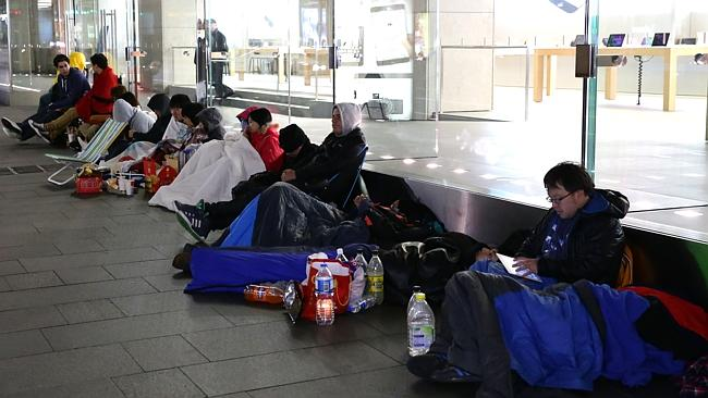 A new breed of geek. Apple fans queue outside the Apple store waiting for the latest gadget to be released.