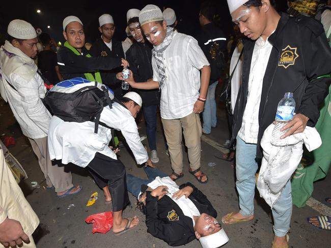 Protesters attend to an injured friend outside the presidential palace after clashes that marred an otherwise peaceful rally against governor Basuki Tjahaja Purnama. Picture: Adek Berry.