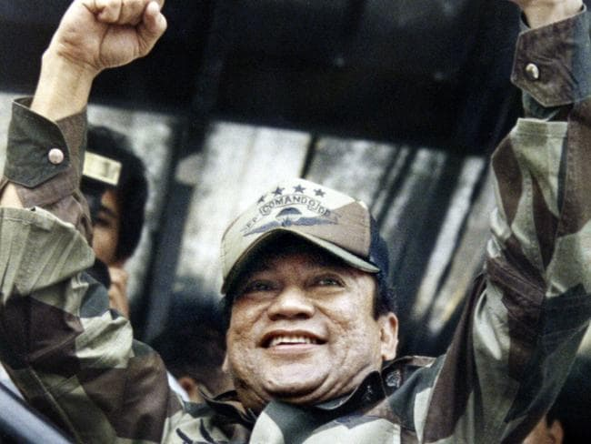 Panamanian military strongman General Manuel Noriega raises his fists to acknowledge the crowd cheers during a Dignity Battalion rally in Panama City, 1988. Picture: AP / John Hopper