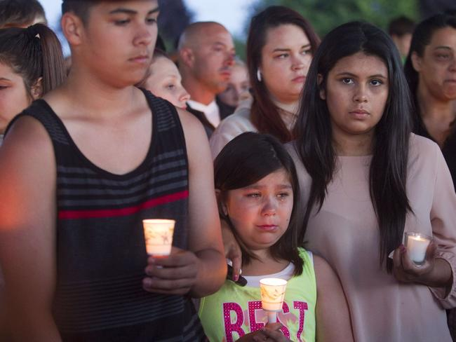 Mourning ... Friends, family and wellwishers hold candles for shooting victim Emilio Hoffman. Picture: Getty