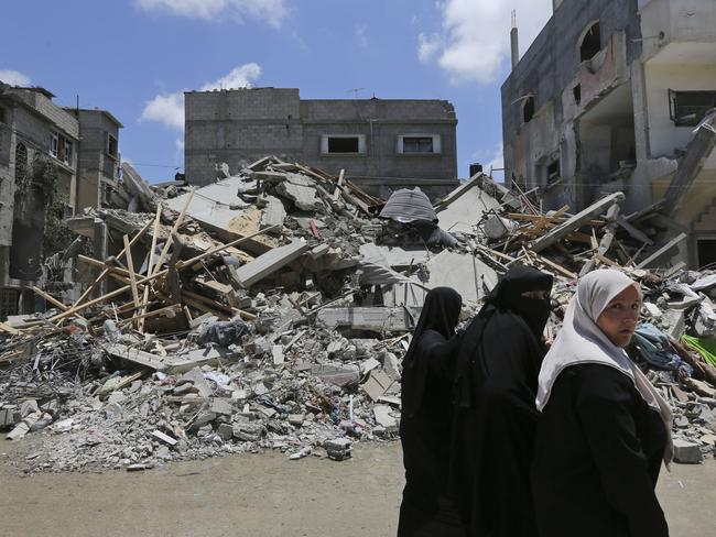Palestinians walk by the rubble of a house destroyed by an overnight Israeli missile strike. AP Photo/Lefteris Pitarakis